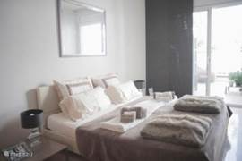 De Master bedroom heeft een eigen badkamer, veel kastruimte en grenst aan het grote terras. Goede matrassen, zowel harde als zachte kussens en naast de paneelgordijnen een rolluik zodat de kamer volledig geblindeerd kan worden.