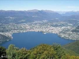 dit is het uizicht van de balcone van Italie je kijkt op de plaats Lugano en een deel van het Lugano meer