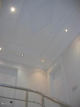 Het plafond in het appartement met een trap naar de 2e etage.