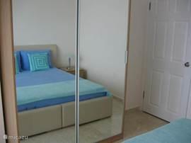 In de slaapkamer op beneden verdieping is een ruime kledingkast en spiegel aanwezig.