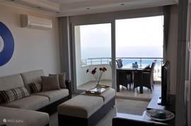 De woonkamer met zit/loungehoek en op de achtergrond de schuifpui met toegang tot het balkon. Hier een rieten tafel met 6 stoelen.