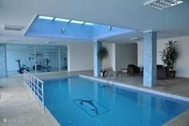 Het binnenzwembad met op de achtergrond de fitness ruimte.