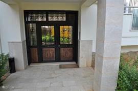 De entree van het appartementenblok. De deur met eigen toegang sleutel bevat een intercom met camera, dus er komen geen ongenode gasten.
