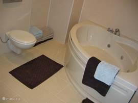 De ruime badkamer met jacuzzi en 2e toilet. Er zijn voldoende badhanddoeken aanwezig.