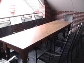 Logia met lange tafel en 8 stoelen met uitzicht aan de voorkant van het huis.