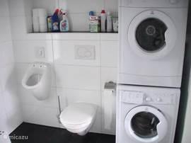 Badkamer op de begane grond met wc, urinoir en wasmachine en droger.