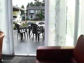 Vanuit de woonkamer komt u via de schuifpui op het ruime terras met tafel en 8 stoelen.