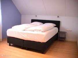 Slaapkamer op de 1e verdieping aan de achterzijde van het huis met een 2-persoons boxspring bed.
