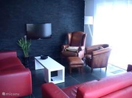 Wohnzimmer mit gemütlicher Sitzecke und LED-TV.