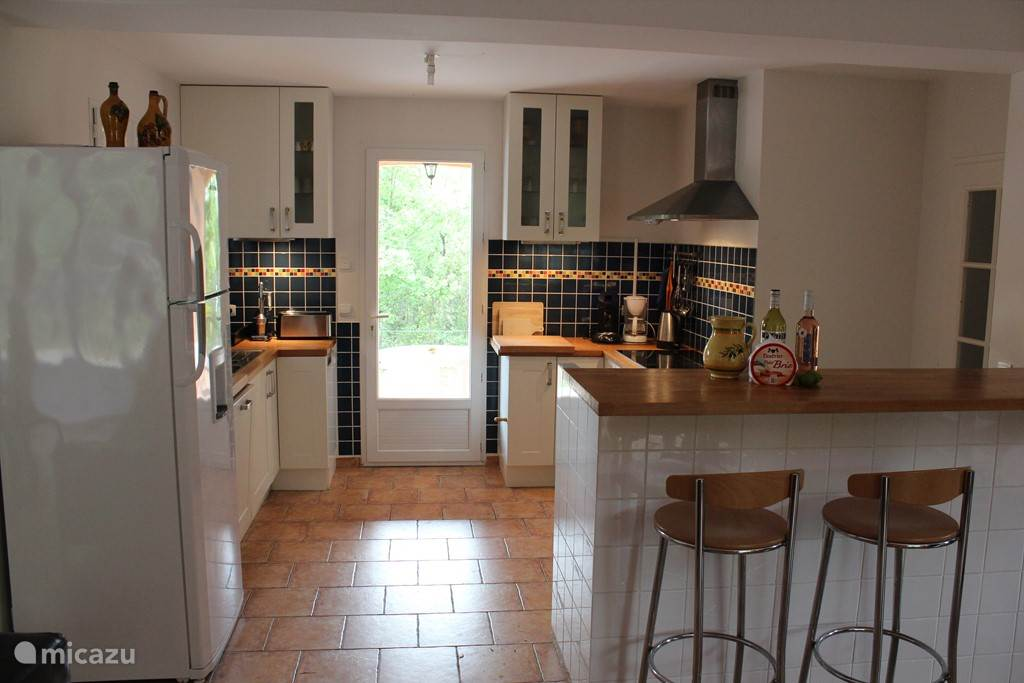 Open kitchen with direct access to the covered terrace and cozy bar with stools.
