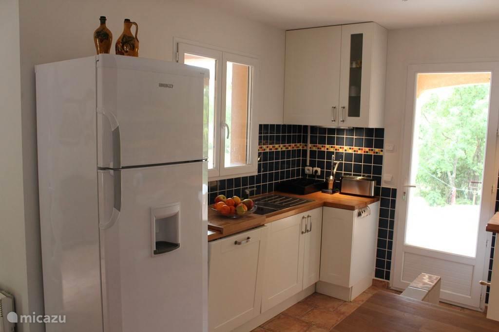 Keuken met ruime koel/vriescombinatie en afwasmachine.