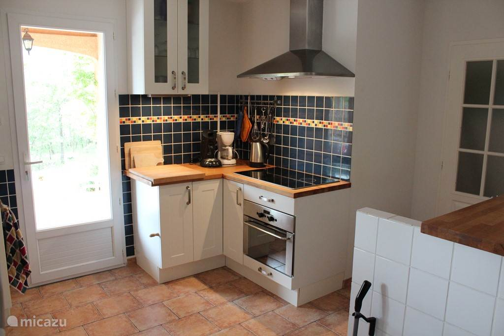 Kitchen with extractor fan, electric hob and oven / grill / microwave.