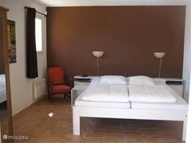 Ruime slaapkamer beneden met eigen badkamer en tuindeuren naar overdekt terras.