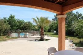 Drie overdekte terrassen met gezellige zitjes. Het zwembad heeft een hek met beveiliging voor kinderen.