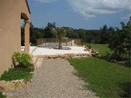 De andere zijkant van het huis. De tuin biedt veel privacy en grenst aan bos.