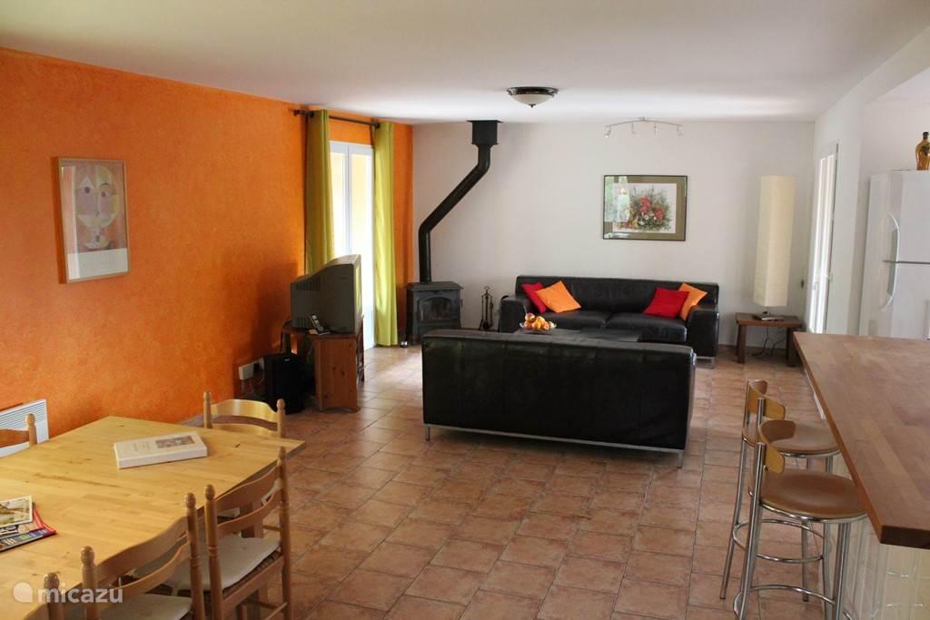 Ruime woonkamer met eethoek tot 12 personen, lekker zithoek, open keuken met bargedeelte en deuren naar de 3 overdekte terrassen.