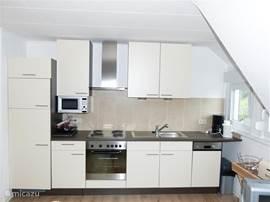 Woonkamer met zicht op open (nieuwe) complete keuken. Vaatwasser, magnetron, elektrisch koken.