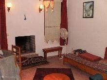 Woonkamer met open haard en 2 bedbanken en eethoek.