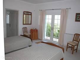 De tweede slaapkamer (airco) op de BG. Ook hier kunt u de deuren openslaan naar de tuin. Links ziet u de deur naar de en suite badkamer.