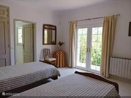 Een van de twee slaapkamers (airco) op de BG. De deuren gaan open naar de tuin, de andere deur naar uw en suite badkamer. De bedden kunnen tegen elkaar aangeschoven worden.