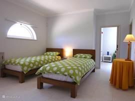 Slaapkamer nummer 4 (airco), op de 1e verdieping met badkamer en suite. De halve ramen kunt u openklappen voor frisse lucht, de horren houden insecten buiten. Ook ziet u de deur naar de gameroom. U raadt het al: hier slapen onze kinderen.