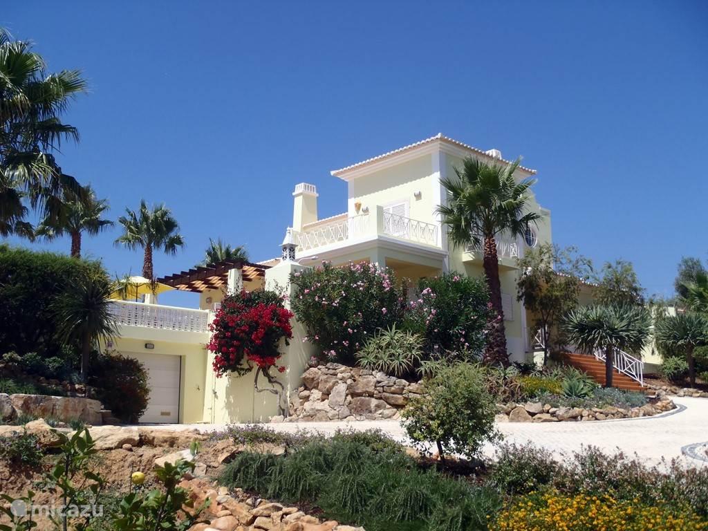 Het huis bezien vanaf de oprijlaan. Het huis is gelegen op een heuvel van waar uw een prachtig uitzicht over de vallei en de Algarve heeft. De ligging garandeert ook uw privacy. Voor uw auto wordt een carport gemaakt (2014) zodat u in de schaduw kan parkeren.
