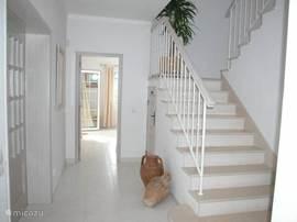 De nastuurstenen trap naar de eerste verdieping. Ook ziet u hier de deur naar een van de twee slaapkamers op de BG en de deur naar de woonkamer.