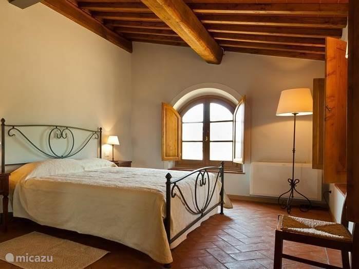 Romantisch smeedijzeren bed en fraai balkenplafond in slaapkamer nr 1.
