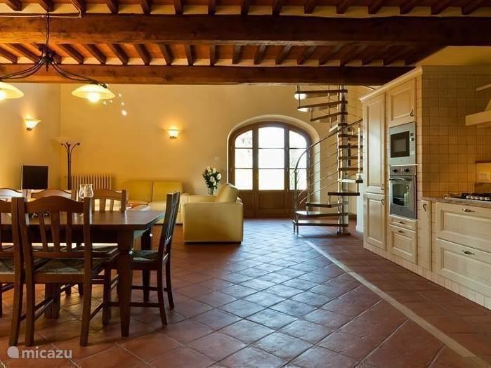 Grote salon met open keuken en eettafel. Antieke terracotta vloeren ingelegd met notenhout Met origineel Toscaans balkenplafond