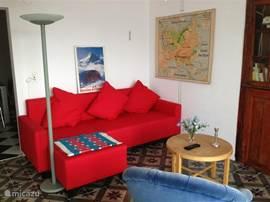 De zitkamer met slaapbank en antieke inbouw-kast waarin zich de flatscreen bevindt.