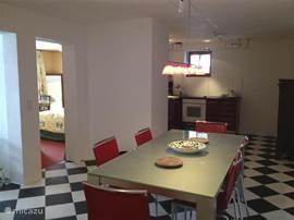 Eetkamer met doorzicht naar de keuken en slaapkamer.
