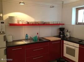 Moderne hoekkeuken met allerhande apparatuur zoals oven, magnetron, afwasmachine, sapcentrifuge.