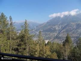 Uitzicht vanaf één van de balkons over de Zwitserse Alpen met bossen, weilanden & besneeuwde toppen.