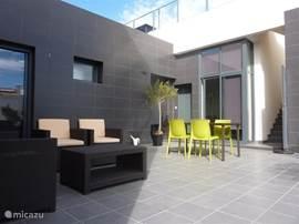 Het zeer ruime gelijkvloers terras met loungeset en tuinset.