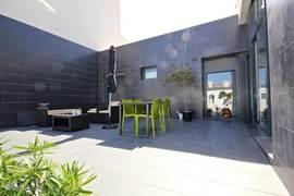 het grote gelijkvloers terras met tuinset en loungeset.