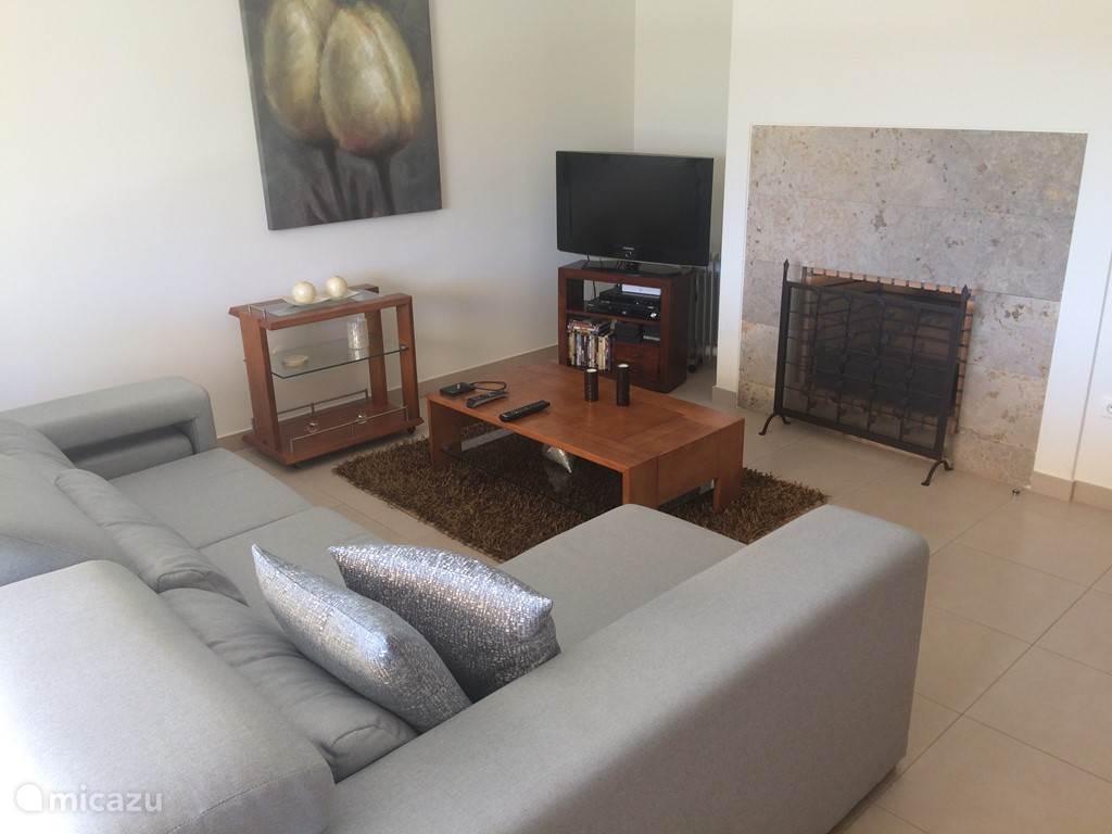 De gezellige woonkamer met open haard en tv.