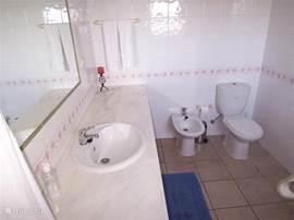 En-suite privé-badkamer bij de hoofdslaapkamer, voorzien van bad, douche, toilet, bidet en wastafel