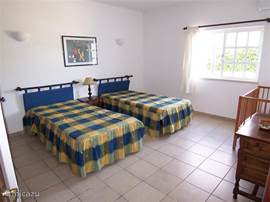 Tweede ruime slaapkamer op de begane grond, met twee grote eenpersoonsbedden die ook aan elkaar geschoven kunnen worden, en een babybedje.
