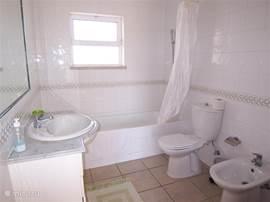 Derde badkamer op de eerste verdieping, met bad, douche, toilet, bidet en wastafel.