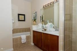 Master badkamer (1). Met dubbele wasbak, ligbad, grote douche-cabine, toilet, linnenkast en grote walk-in-closet