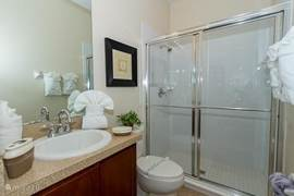 Badkamer (2) Met wastafel, toilet en grote douche-cabine. Deze badkamer heeft ook een rechtstreekse deur naar buiten/zwembad, zodat er vanuit buiten en zwembad gebruik kan worden gemaakt van de douche en toilet (zonder eerst de villa/woonkamer eerst in te moeten).