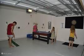 Garage/gameroom. De garage hebben we omgebouwd tot gameroom met: tafeltennis/shuffleboard, airhockey, tafelvoetbal, minigolf, darts en basketbalspel. Ook materialen beschikbaar voor tennis, badminton, volleybal en allerlei andere spellen en speelgoed.