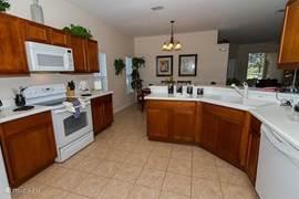 Vanuit de keuken uitzicht op de eetkamer. Met dubbele wasbakken, vaatwasser, koffieapparaat, waterkoker, etc.