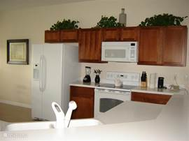 De keuken vanuit de andere kant bekeken met Amerikaanse koel/vriescombinatie, grote oven, magnetron, keramische kookplaat, blender, broodrooster, etc.