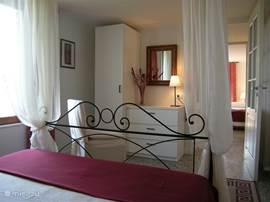 Kleine suite, doorkijkje van de hemelbedkamer naar hal met kleine badkamer, aansluitend de andere slaapkamer.