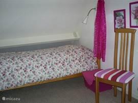 2 slaapkamers boven met eigen kleur. Dit is de roze kamer: 3 eenpersoonbedden + nachtlampje,stoel + wastafel
