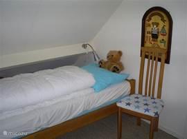 2 slaapkamers boven met eigen kleur. Dit is de blauwe kamer: 2 eenpersoonbedden + nachtlampjes,stoel + kinderledikantje