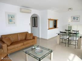 Woonkamer vanuit een ander perspectief. Grenzend aan de woonkamer bevindt zich een terras voorzien van eettafel en stoelen.
