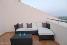 Luxe loungeset op het terras boven welke een vrij uitzicht en volop privacy biedt. Het terras is voorzien van een zonnescherm.