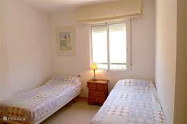 Slaapkamer op de begane grond met twee separate bedden en inbouw kledingkast.